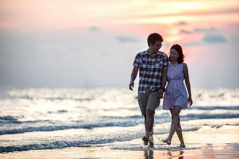 Cặp đôi đang đi dạo bên bờ biển