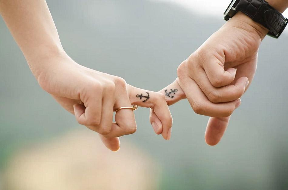 Hình xăm mỏ neo trên ngón tay của một cặp đôi