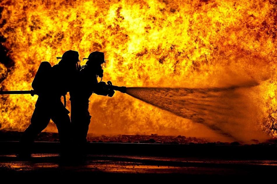 Hai người lính cứu hỏa đang xịt nước vào trong đám lửa