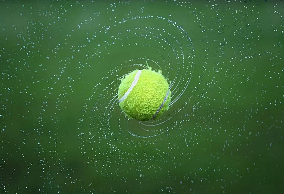 Quả bong tennis ướt nước đang xoay tạo thành các vòng xoáy nước